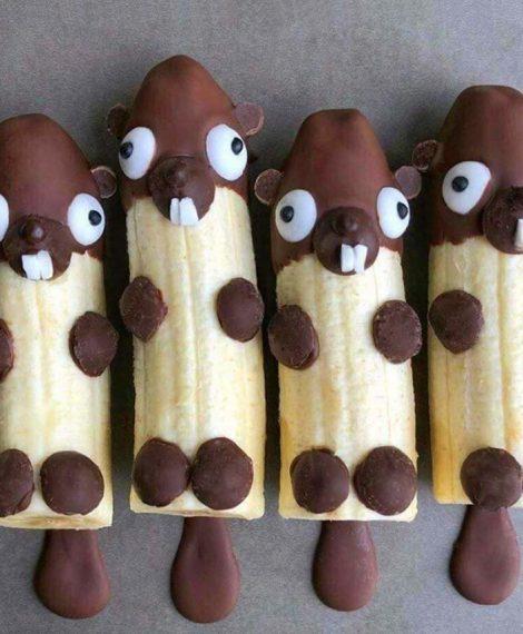 Bananenbiber. Kleine Biber aus Schokoladenguss, geteilten Bananen und Zuckerguss.